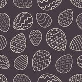 Monochrome Easter pattern with outline eggs. Monochrome Easter seamless pattern with white outline eggs on dark background. Ornate doodle hand drawn eggs texture Royalty Free Stock Image
