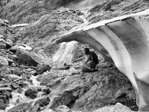 Monochrome image adult woman with backpack sitting on a rock under a block of ice Stock Photo