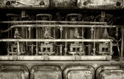 Monochrome image of a big old old rusting petrol engine with details of pipes bolts and cylinders. Dark monochrome image of a big old old rusting petrol engine royalty free stock image