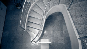 Monochrome image of curved stoned staircase at modern building Royalty Free Stock Photos