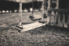 Monochrome image empty swing at the playground in summer, horizo Royalty Free Stock Images
