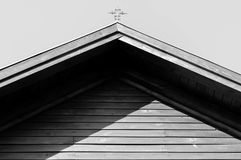 Monochrome image of iron catholic cross on residentual house rooftop. In harsh sunlight, dark shadows royalty free stock images