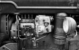 Monochrome image of a large old petrol engine with rust and old stains in a dark agricultural vehicle with headlight. A monochrome image of a large old petrol stock photos