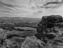 Monochrome image of a large stone outcrop known as great rock in todmorden west yorkshire with overcast sky and pennine royalty free stock photo