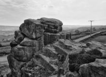Monochrome image of a large stone outcrop known as great rock in todmorden west yorkshire with overcast sky surrounding fields royalty free stock images