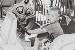 Monochrome image of little boy driving toy child car Royalty Free Stock Photo
