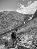 Monochrome image lone traveler with a backpack sitting on a rock and looking at the snowy mountains Stock Image