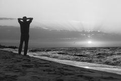 Monochrome image of man at sunrise on beach Stock Images