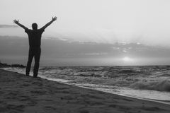Monochrome image. Man welcomes the sunrise on beach Stock Photography