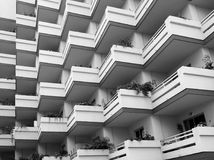 Monochrome image of repeating balconies on large modern concrete apartment building with house plants stock images