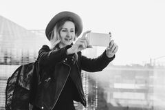 Monochrome image.Tourist woman in hat with backpack stands at airport, takes photos, shoots video on smartphone`s camera stock image