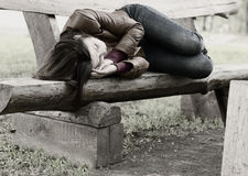 Monochrome image of a woman on a park bench. Monochrome image woman lying curled up sleeping on rustic wooden park bench, conceptual of homelessness, exhaustion Royalty Free Stock Photography