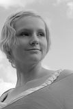 Monochrome image of young caucasian woman against a pale sky Royalty Free Stock Photo