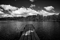 Monochrome lake with clouds. Lake with clouds above and footbridge Royalty Free Stock Images