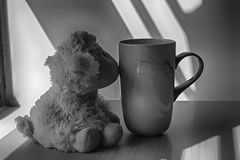 Monochrome Lamb toy with cup sitting by the window in shadows royalty free stock photo
