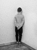 Monochrome of a lonely little boy who is standing corner of the room Royalty Free Stock Image