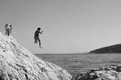 Monochrome Man jumping off rock into unknown water Royalty Free Stock Photos