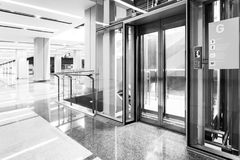 Monochrome Modern steel elevator doors cabins in a business lobby or Hotel, Store, interior, office,perspective wide angle. Three. Elevators in hotel lobby stock image
