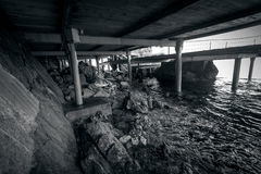 Monochrome  photo of beach under the old wooden pier Royalty Free Stock Image