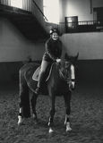 Monochrome  photo of beautiful woman riding horse in manege Stock Photography