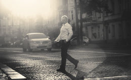 Monochrome photo of businessman crossing road at sunny day Stock Images