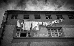 Monochrome photo of clothes drying outside of grungy building Stock Images