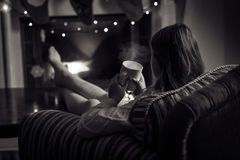 Monochrome photo of cute woman sitting at fireplace with cup of Stock Photography