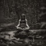 Monochrome photo of european woman sitting in forest alone and meditating royalty free stock images