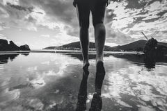 Monochrome photo of female legs walking on water with sky reflec Stock Images