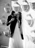 Monochrome photo of groom covering bride with jacket Stock Images