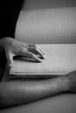 Monochrome photo of hand reading braile text Stock Photography