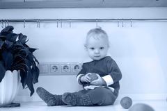 Monochrome photo of little child in the kitchen sits on a table stock images