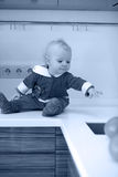 Monochrome photo of little child in the kitchen sits on a table royalty free stock photography