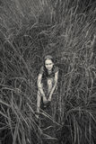 Monochrome photo of lonely girl sitting in grass at field Stock Photo