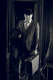 Monochrome photo of man in hat with suitcase walking in the trai Stock Photography