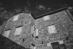 Monochrome photo of old stone house at sunny day Royalty Free Stock Image