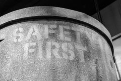 Safety first sign on large bucket. Monochrome photo of `Safety First` sign on the side of a large bucket Royalty Free Stock Image