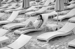 Monochrome photo of sexy woman in dress lying on sunbed Royalty Free Stock Photo
