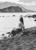 Monochrome photo of sexy woman sitting on rock at deserted beach Royalty Free Stock Images