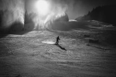 Monochrome photo of skier riding on slope at sunny day Stock Photos