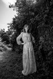 Monochrome photo of woman in long dress at forest Stock Photo