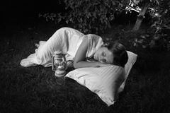 Monochrome photo of woman sleeping at garden at night Stock Image