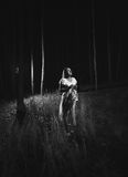 Monochrome photo of woman in white dress walking at forest at ni Stock Image