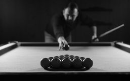 Monochrome photo young man playing billiards royalty free stock image