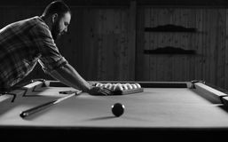 Monochrome photo young man playing billiards royalty free stock photos