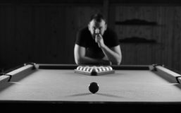 Monochrome photo young man playing billiards Stock Images