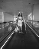 Monochrome photo of young woman standing on escalator at airport Stock Images