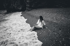 Monochrome photo of young woman in white shirt lying on sea beac Royalty Free Stock Photos