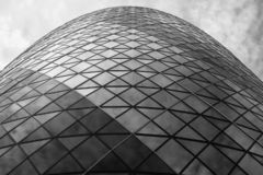 Monochrome photograph looking up at the iconic Gherkin Building, 30 St Mary Axe in the City of London, UK