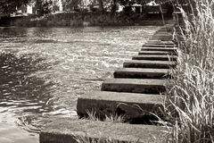 Monochrome photograph of stepping stones. A high quality monochrome photograph of stepping stones over a river Royalty Free Stock Images
